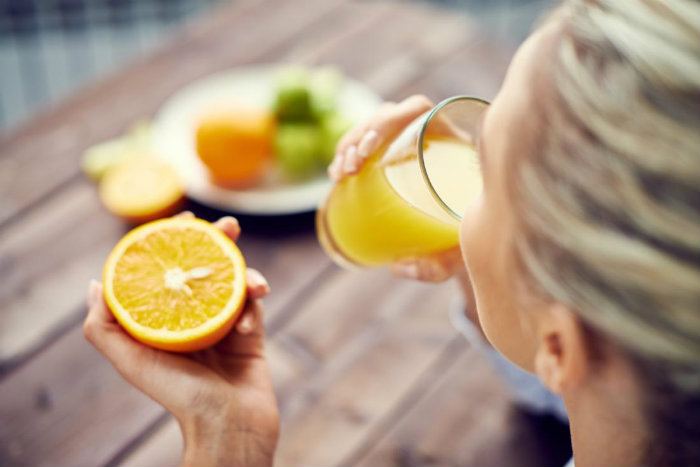 a-woman-drinking-orange-juice-and-holding-an-orange-vitamins