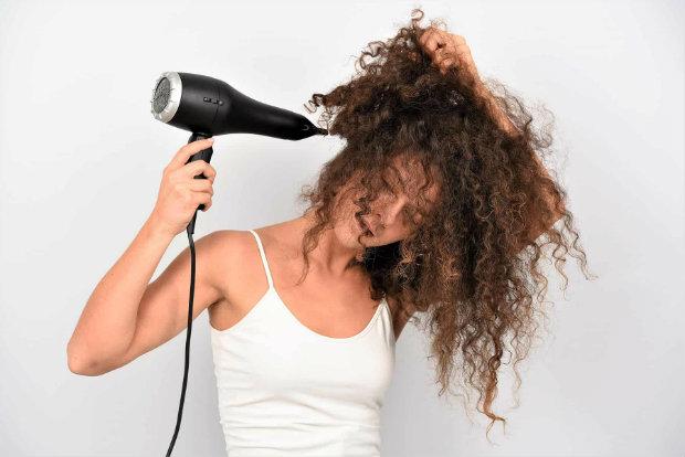 cute girl using hair dryer