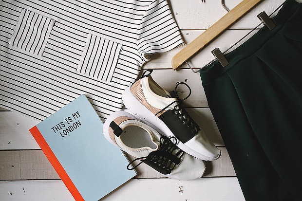 picture of girls t-shirt whit stripes, black skirt, a notebook and sneakers on white wooden background