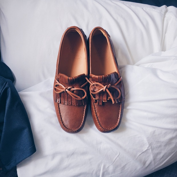 picture of brown loafers on white bedsheet beside blue t-shirt