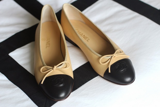picture of beige and black chanel ballerina flats on white with black lines background