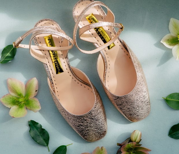 picture of statement shoes in silver color on a blue background with flowers all around