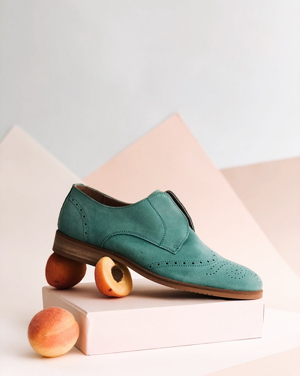 picture of bluish leather flats on blue and pink box and peaches around