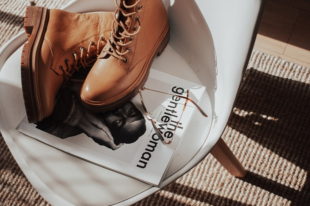 picture of brown flat boots on a white  chair over a magazine and sunglasses on the side