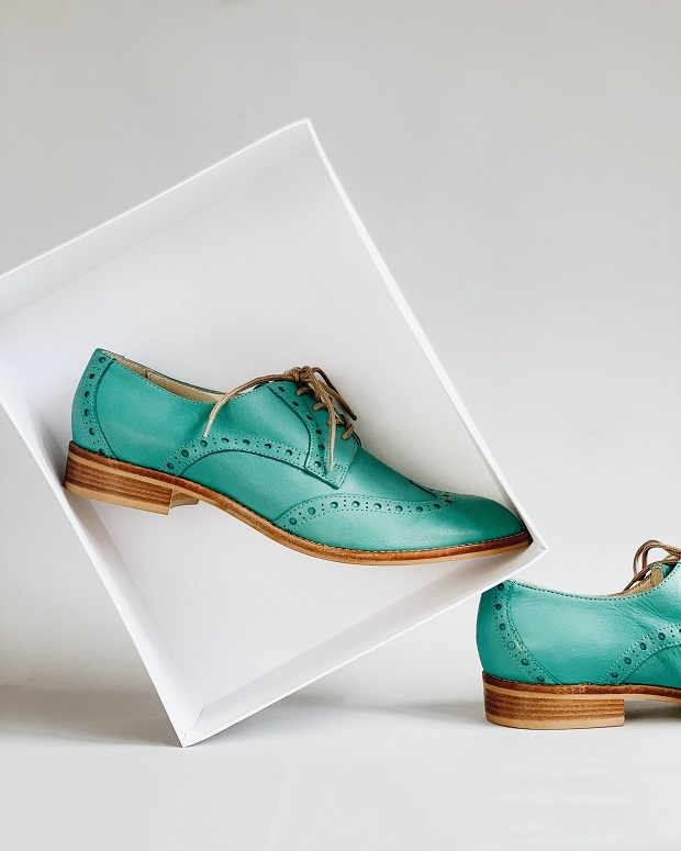 green flat leather oxfords shoes in a box and a white background