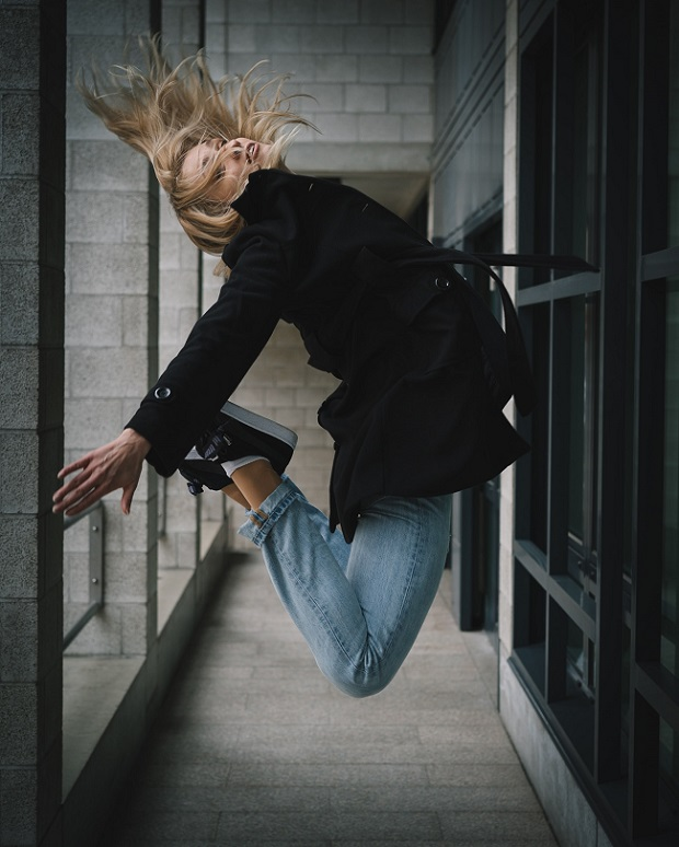 picture of a girl jumping on a hallway in building wearing black jacket, jeans and sneakers