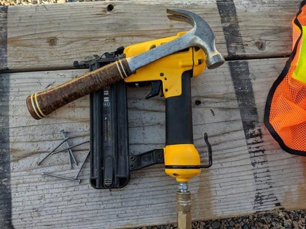 Close-up of hammer and nail gun