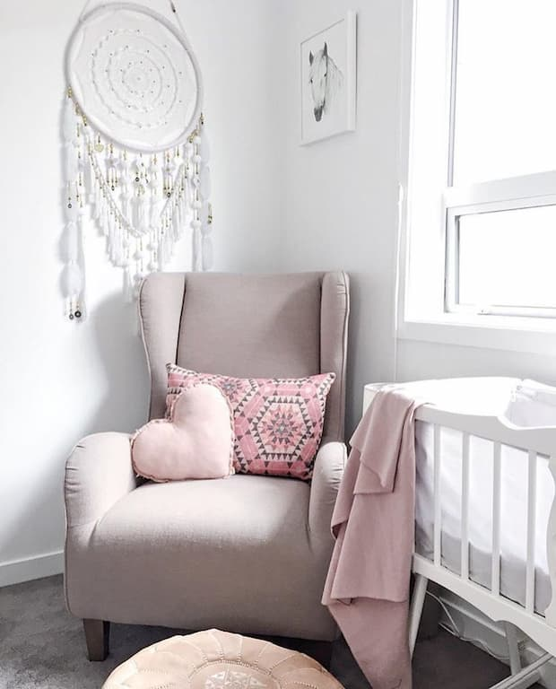 pink nursing chair with decorative pillows near baby's bed