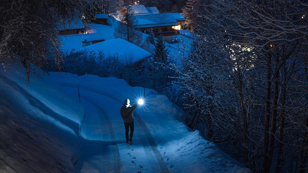 picture of a place with a lot of snow and a person with a Led torch on the road