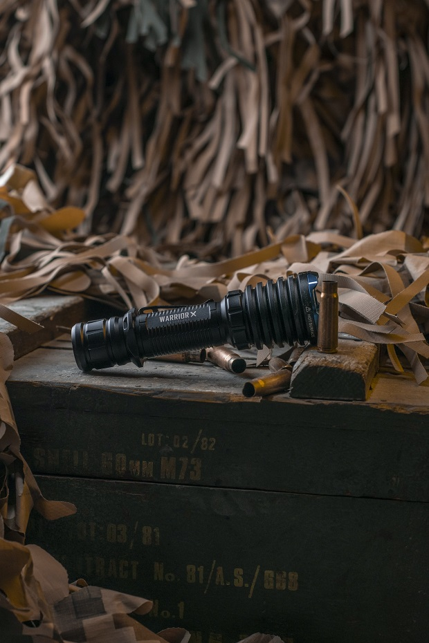 picture of black Olight torch on a wooden table in a working shop