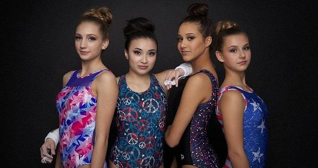 Four girls in gymnastics leotards