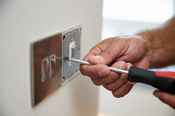 Close Up Of Electrician Repairing Domestic Light Switch