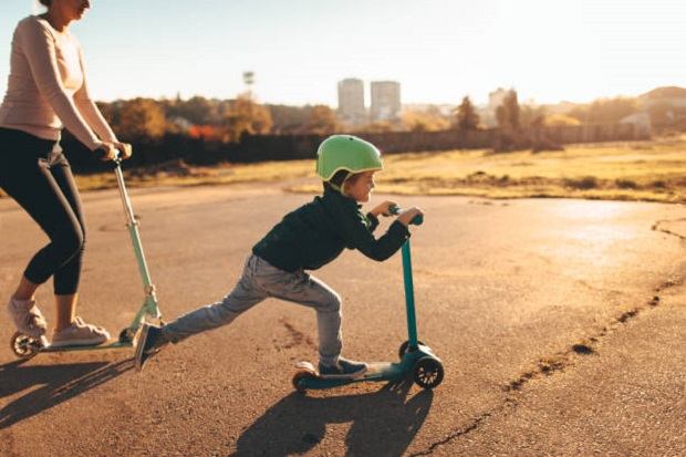 cheerful little boy riding a push scooter