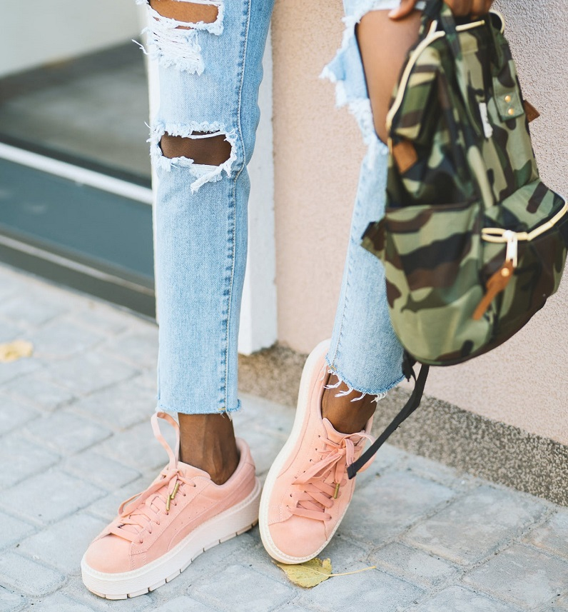 picture of person wearing jeans, pink shoes and a backpack  standing on a sideway